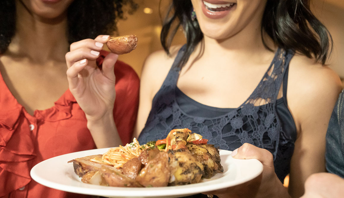 Close up of woman taking a potato from a plate of chicken, salad and potatoes
