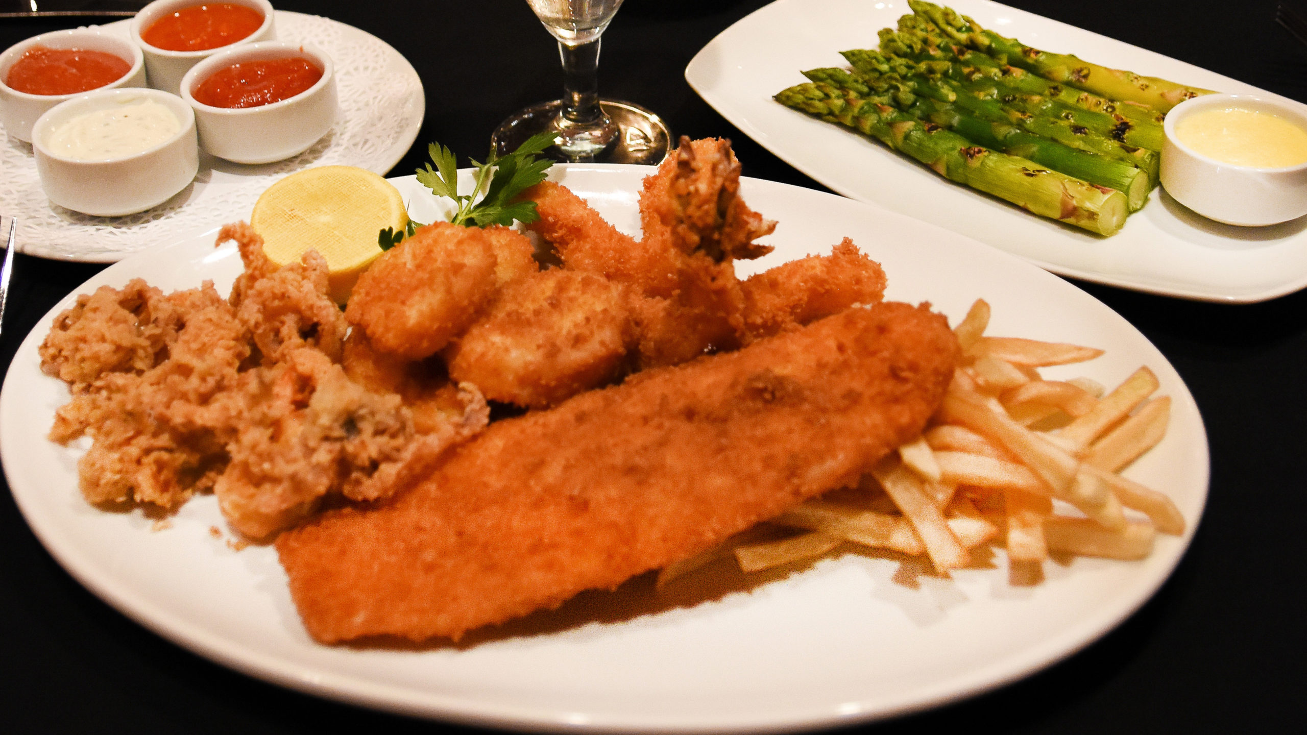 plate of fried fish, shrimp and calamari with a side dish of asparagus