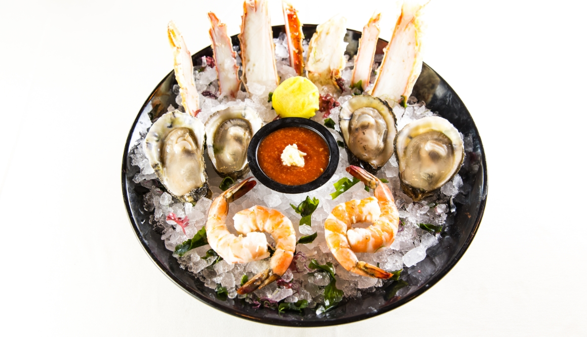 Black bowl with crab, oysters, shimp and shrimp sauce