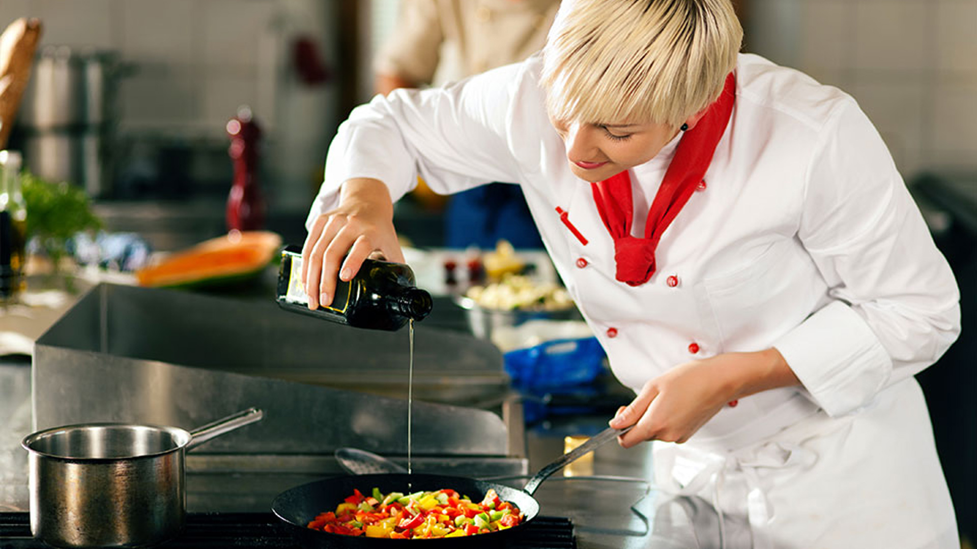 Woman chef pouring olive oil into a skillet of pepper on a stove