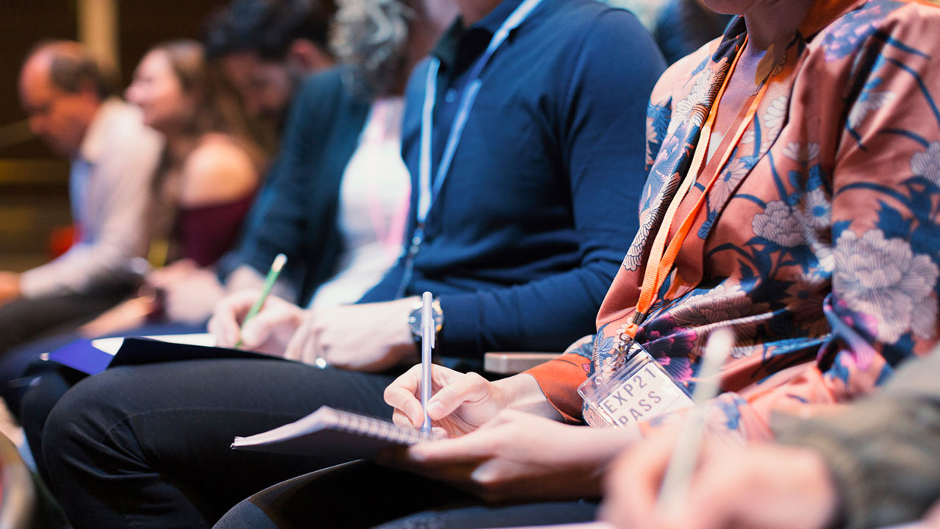 close up of two women taking notes at a convention