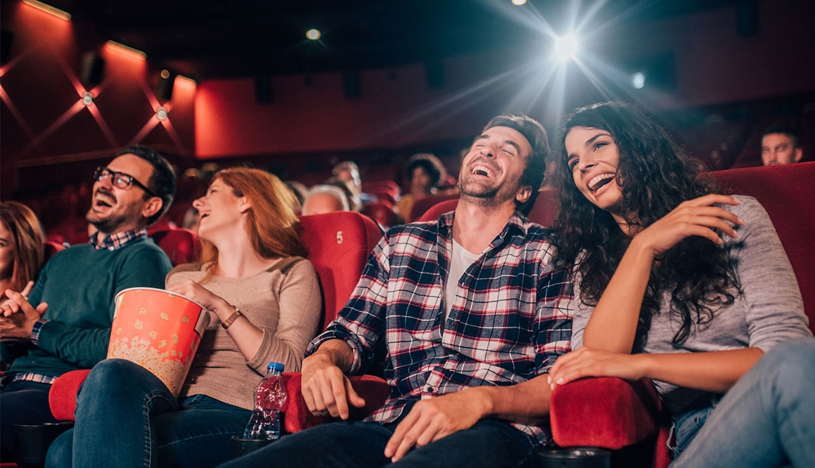 Two couples in a movie theater seats laughing