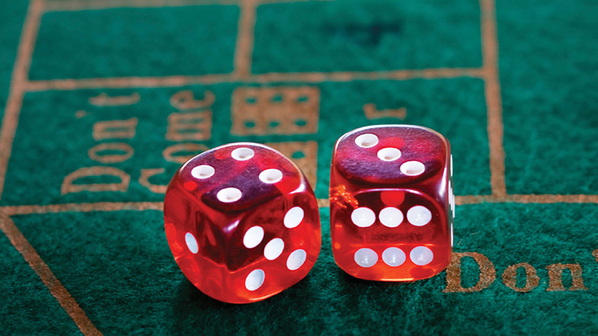 Dice showing 4 and 3 sitting on a green felt craps table
