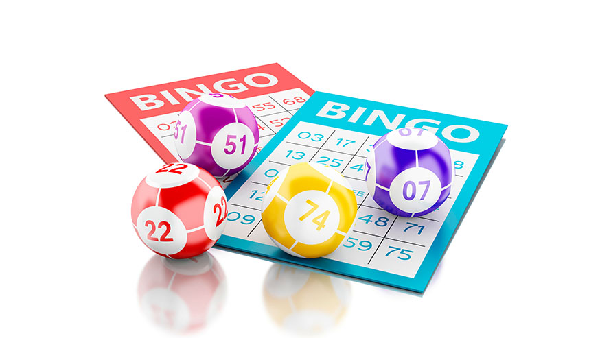 Bingo cards and numbered ball on white table