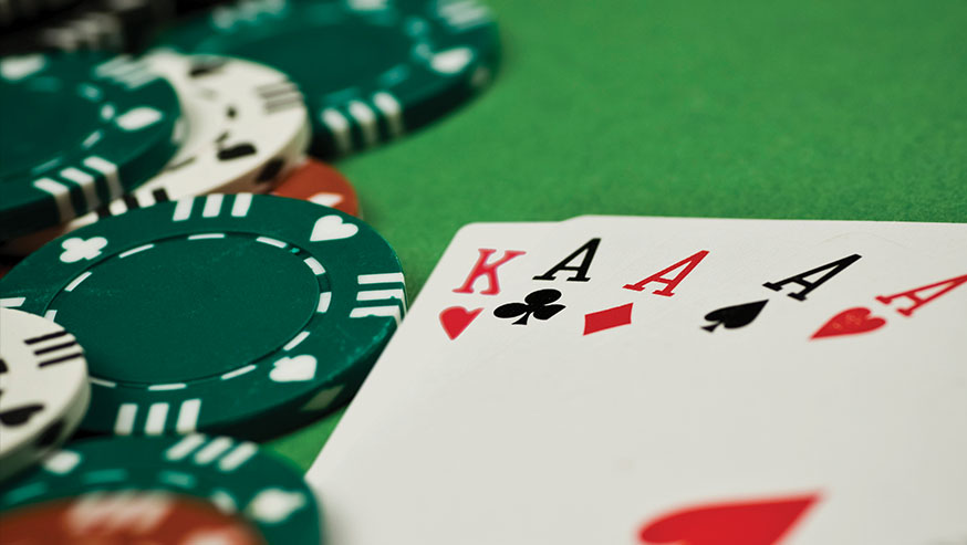 King, four aces, poker chips on a green felt table