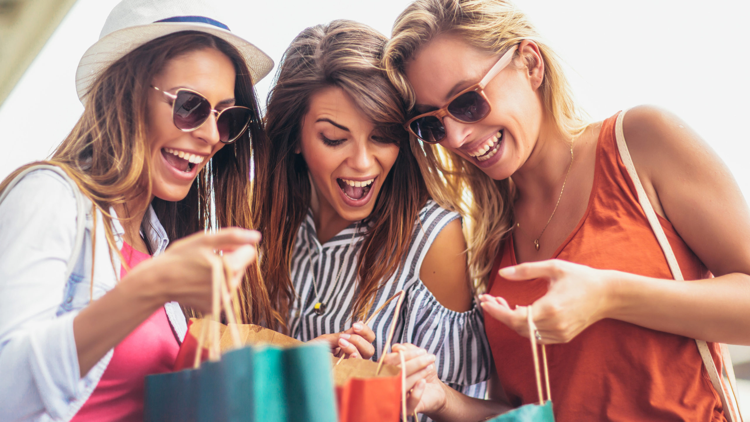 Three women in summer clothing laughing and showing what bought shopping